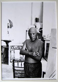 Cannes, 1957 (Picasso standing in white shorts in front of some canvases) by Andre Villers
